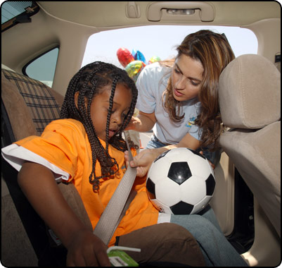 adult helping child with seatbelt in car