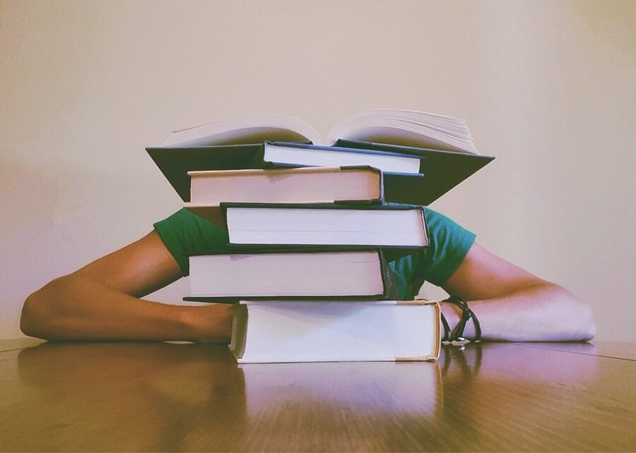 student with head on table behind stack of books