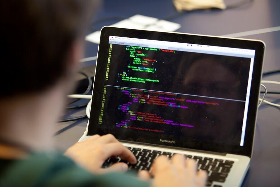 man using code language on laptop