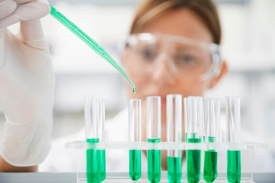 scientist pouring green liquid in several flasks in the lab