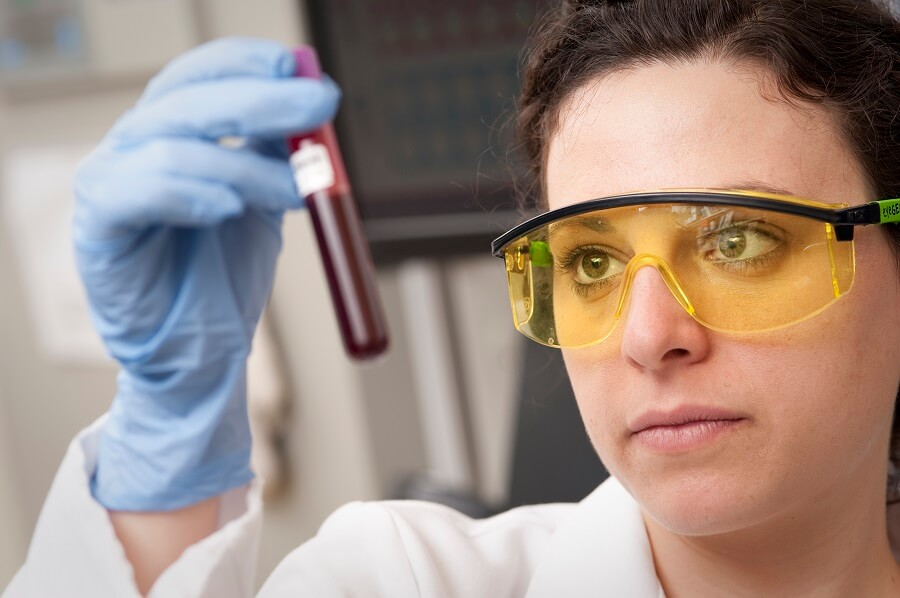 scientist looking at a sample of blood in a flask