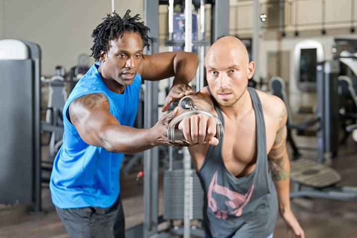 personal fitness trainer helping a client lift weights