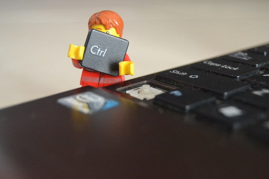 toy figurine holding the ctrl key of a keyboard
