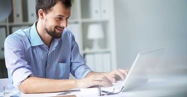 man smiling as he uses his laptop