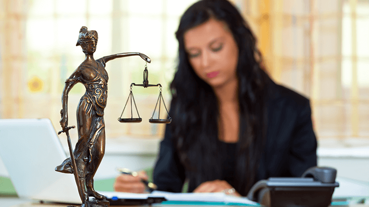woman at her desk with the statue of Lady Justice in front of her