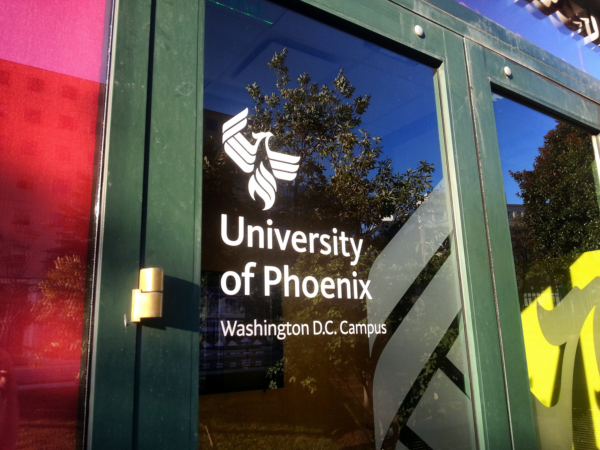 a glass door with name and logo of a University