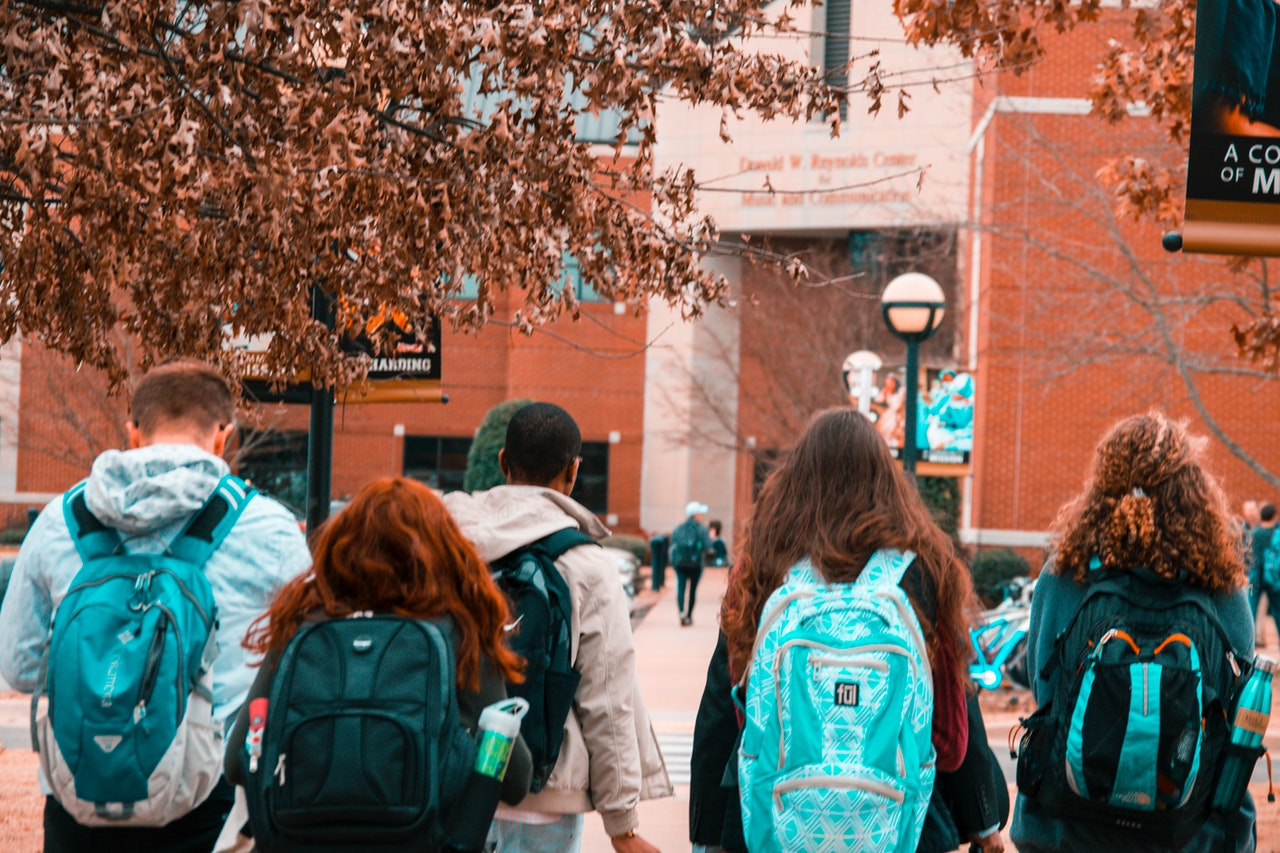 students with green and blue backpacks facing red brick building in the autumn and are about to cross the street